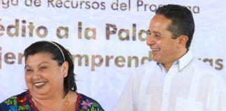 El gobernador Carlos Joaquín entrega un cheque simbólico a una mujer emprendedora.