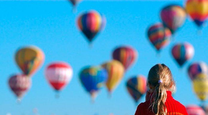 Niña observa asombrada el despegue de cientos de globos en el festival de León